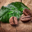 Stock Photo: Coffee grains and green leaf