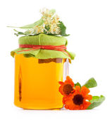 Honey in glass jar with flowers — Stock Photo