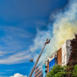Stock Photo: Firemen on ladder extinguishing fire