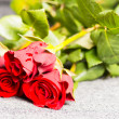 Three red roses on a cloth — Stockfoto