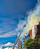 Firemen on a ladder extinguishing fire — Stock Photo