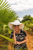 Young woman in hat and sun glasses near palm — Stock Photo