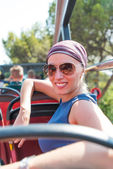 Smiling woman in sunglasses and bandana on bus — Stockfoto