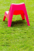 Red plastic chair on green grass — Stock Photo