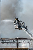 Firemen on a lift — Stock Photo