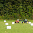 Tractor and Bales of a green crop - Stock Photo