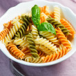 Spiral pasta and basil in bowl - Stock Photo
