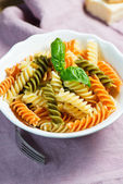 Spiral pasta and basil in bowl — Stock Photo