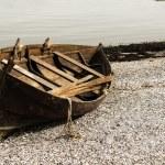 Wooden boat on gravel beach — Stock Photo #19578689