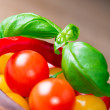 Basil leafs with tomatoes and pepper in wooden bowl — Stock Photo #21180183