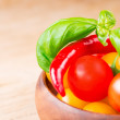 Basil leafs with cherry tomatoes and chili pepper in wooden bowl — Stock Photo #21181135
