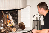 Fixing fire in fireplace — Stock Photo