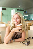 Blond woman drinking coffee and smiling — Stock Photo