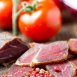 Stock Photo: Slices of cured meet on wooden table