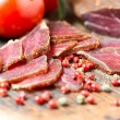 Stock Photo: Slices of cured meet on wooden table angled view