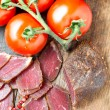Stock Photo: Slices of cured meet on wooden table top view