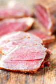 Slices of cured meet and pepper on table close up — Stock Photo