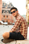 Young handsome man sitting on street — Stock Photo