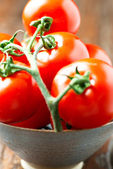 Tomatoes in a bowl on old wooden table vertical macro — Stock Photo
