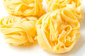Dry pasta tagliatelle on tablecloth — Stock Photo