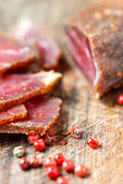 Slices of cured meet and pepper on table — Stock Photo