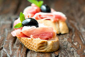 Sandwiches with prosciutto olive on wooden old table horizontal — Stock Photo