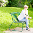 Young woman sitting on bench in park and smiling — Stock Photo
