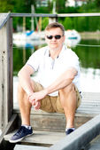 Mature man with sunglasses sitting at pier — Stock Photo