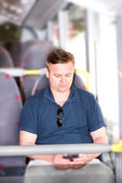 Man traveling on bus and using his smartphone — Stock Photo