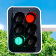 Red and green traffic lights on blue sky — Stock Photo #27660913