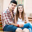 Young couple sitting on bench on street — Stock Photo