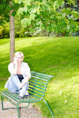 Young woman sitting on bench in park — Stock Photo