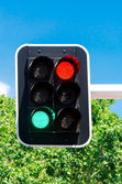 Red and green traffic lights on blue sky — Stock Photo