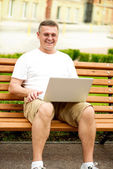 Man with laptop sitting on bench — Stock Photo