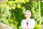 Attractive eastern europe blond smiling portrait in park — Stock Photo