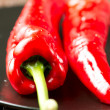 Red chilli peppers on black plate on wooden table close up — Stock Photo #32028867