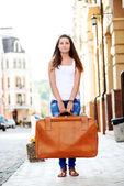 Girl with luggage in city — Zdjęcie stockowe