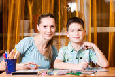 Mother and boy doing homework — Stock Photo