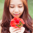 Girl with a red flower and a butterfly — Stock Photo
