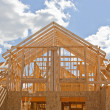 New residential construction home framing against a blue sky — Stock Photo #13363031