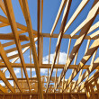 Stock Photo: New residential construction home framing against blue sky