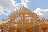 New residential construction home framing against a blue sky — Foto de Stock