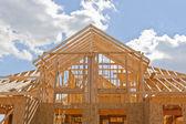 Encuadre casa de nueva construcción residencial contra un cielo azul — Foto de Stock