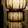 Whisky or bourbon barrels aging in a distillery warehouse -  
