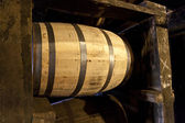 Whisky or bourbon barrels aging in a distillery warehouse — Stok fotoğraf