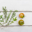 Homegrown herbs and tomatoes on rustic wood board — Stock Photo