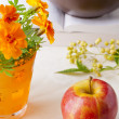 Red apple and orange flowers on a table — Stockfoto