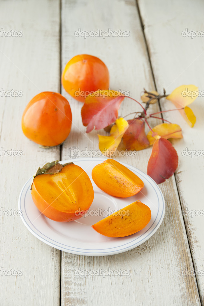 Ripe persimmon with cut on a plate, selective focus — Stock Photo #16241671