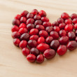 Cranberries in heart shape on wooden board. - Stock Photo