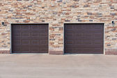 Two garage doors on brick wall. — Foto de Stock